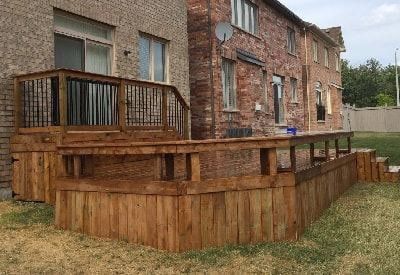 backyard deck in pressure treated wood with wood railings bench and stairs